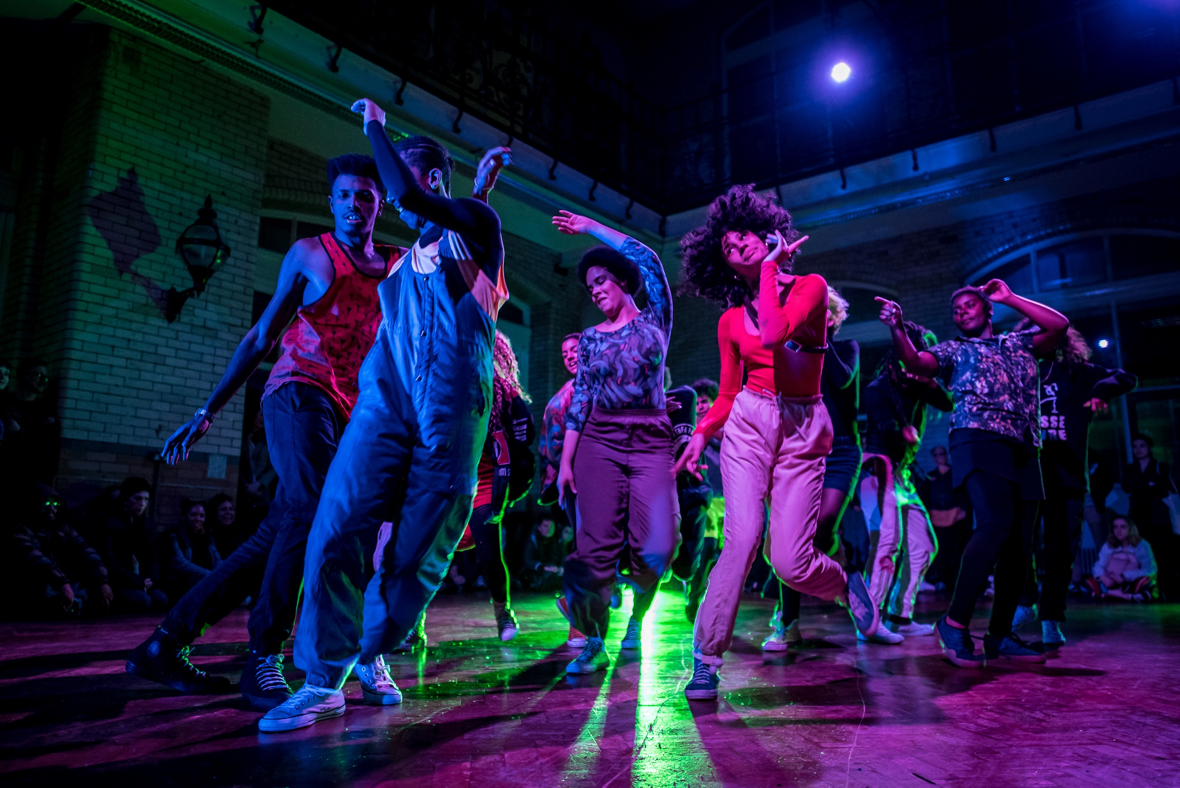 Image: When It Breaks It Burns. A group of young people dancing under multi-coloured lights. Photo by JMA Photography.