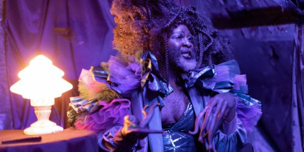 An image of a person with a black and silver beard, large hair decorated with braids sitting next to a lamp on a table. They wear a silver costume with pink and purple ruffled shoulders and have pink tentacles attached to their fingers.