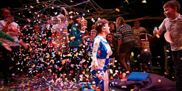 Jess Thom, a woman with short brown curly hair wearing a blue and silver superhero suit, is surrounded by children throwing confetti
