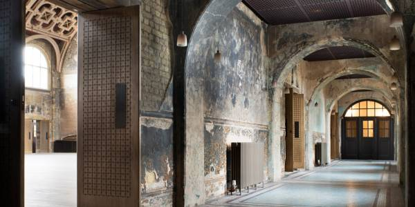 A corridor off the Grand Hall, with arches and fire-burnt plaster walls. Through a heavy wooden door on the left hand side, a sliver of the grand hall and the lattice wood ceiling are visible