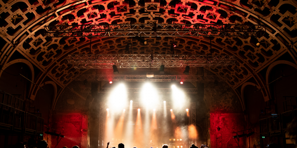 A photo taken from behind a crowd gathered at a concert in our Grand Hall. Spotlights shine down from the wooden lattice roof and illuminate the stage.