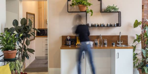 An image of a blurred figure making coffee in the Scratch Hub reception, a single sink unit sits beneath a decorative shelf with large green plants.
