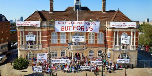 Crowds of people spill out of Battersea Arts Centre's front doors and every balcony. Banners draped across the building read 'Dear President Trump', 'Not For Me, Not For You, But For Us', 'Difference is beautiful', 'Women are powerful', 'More art now', 'Everyone is creative', 'Build bridges not walls', 'United we stand', 'We are open', '#BACPhoenix', 'Love Battersea Arts Centre'.