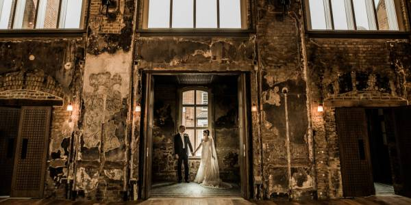 An image of a married couple stood holding hands in the door way into the Grand Hall.