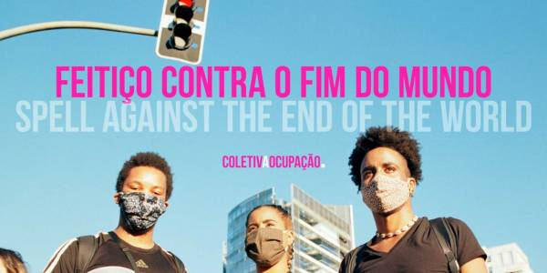 Feitico contra o fim do mundo (pink text), translated as Spell Against The End Of The World (grey text), on a blue sky background. Three people wearing fabric facemasks look down to the camera, with a traffic light and skyscraper visible in the background