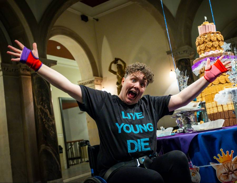 Jess Thom, a woman with short brown curly hair, holds her arms wide in front of a table decorated with cats-in-party-hats bunting and a giant tiered biscuit installation. Photo by Samuel Dore.