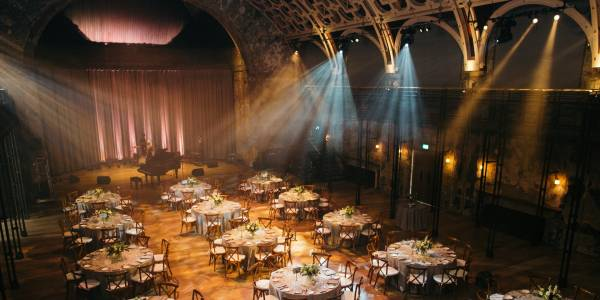 An image of the Grand Hall set up for a wedding. There are lines of circular tables dressed with white table-cloths and flower bouquets. There is a grand piano at the far end of the room and spotlights shining down from the ceiling.