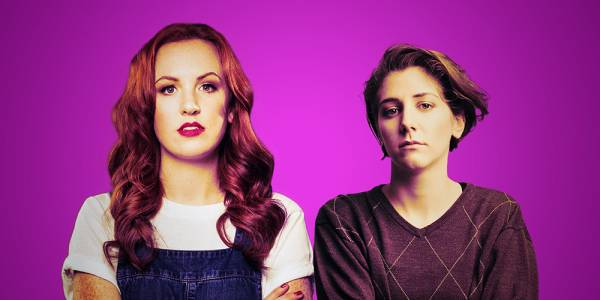 Two white women look ahead at the camera, against a purple background.