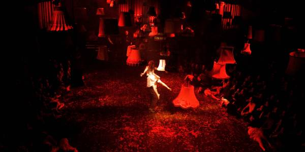 An image from the show Mask of the Red Death. A red hue lights the stage as audience sit cross legged on either side. Light shades hang suspended from the ceiling as a woman dressed in white floats in the centre.