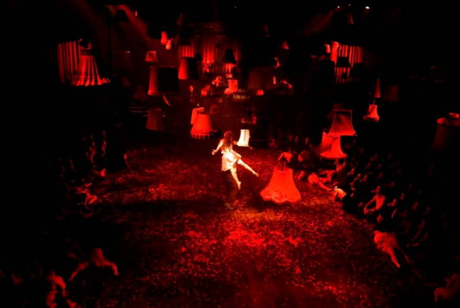 A girl appears to float in the middle of a red lit room, with a number of lampshades also suspended