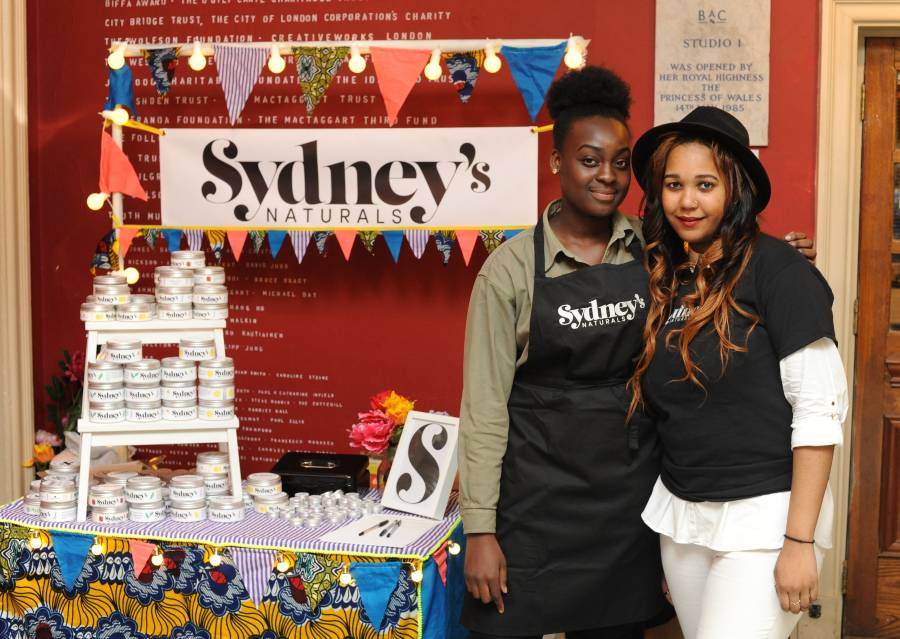 Against a red wall, a stall with colourful bunting is set up for Sydney's Naturals, with lots of branded tins, a colourful tablecloth, and flowers. Sydney, wearing a black branded apron and green shirt, and another agent, wearing a black fedora, branded black t shirt, and white trousers, stand to the right of the stall
