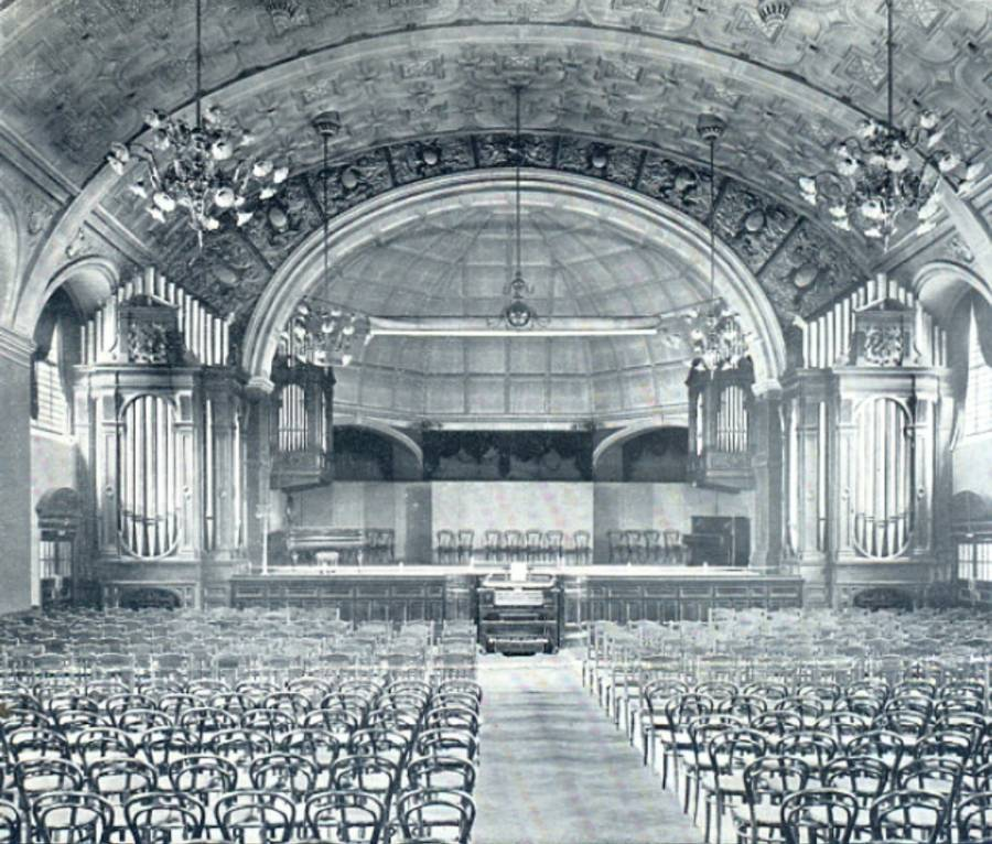 A black and white image of the grand hall, with chandeliers hanging from the ceiling, organ pipes on each side of the stage, the organ console in the middle in front of the stage, and chairs laid out all through the hall with an aisle in the middle