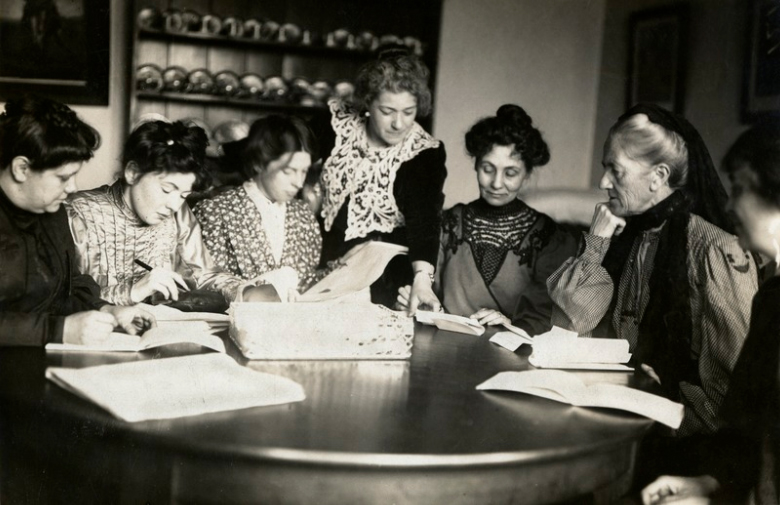 A black and white photograph of seven women around a table, with open books and papers. Six are sitting, one stands in the middle pointing at something in one of the books