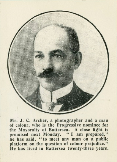 A black and white dappled photo in a cirlce of John Archer, ,a man with a moustache and a balding head. The caption reads 'Mr J C Archer, a photographer and a man of colour, who is the Progressive nominee for the Mayoralty of Battersea. A close fight is promised next Monday.