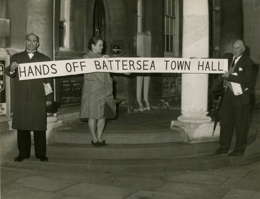 A black and white photograph of three people on the steps of our building, holding a banner reading 'Hands off Battersea Town Hall'.