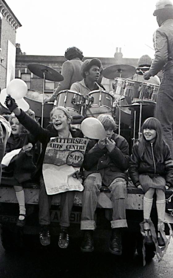 A black and white photograph of a young man playing a drum kit, while in front of him four children sit with their legs hanign off the stage, holding balloons. One girl with glasses holds a poster which says 'Battersea Arts Centre' at the top