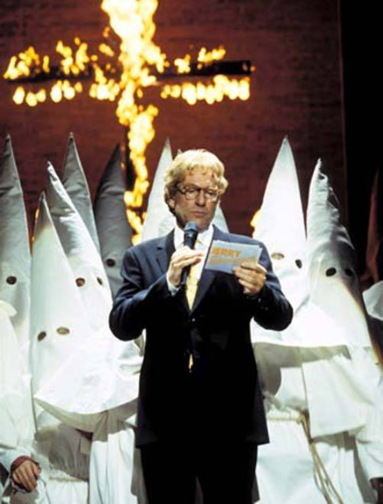 A still from 'Jerry Springer The Opera'. A cross burns in the background as a man with blonde hair and glasses in a suit stands in front of a group of people in white pointy hoods and robes. The man holds a microphone and Jerry Springer cue cards.
