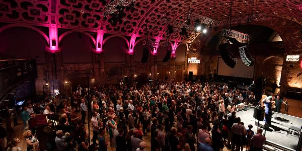 A large standing crowd in the Grand Hall, with the ceiling lit up pink. A stage in the middle of the right hand side has a musician and a harp. Projected onto the far wall are logos for BBC Radio and BBC Proms