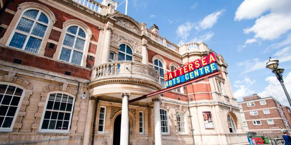 The front of our building, a Victorian town hall made from pale stone and red brick. The Battersea Arts Centre sign is extended from the entrance in red and blue with yellow lettering.