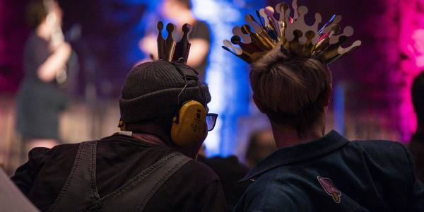 The back silhouette of two figures one wearing ear defenders and the other wearing several paper crowns.