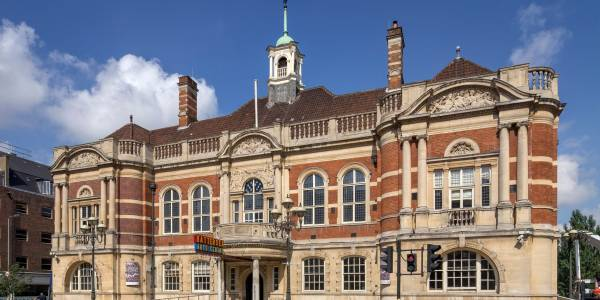 The front of our building, a Victorian town hall, with pale stone on the ground floor, red bricks on the first floor with pale columns and outlines on the windows, and a balcony around the roof. Our red, blue and yellow sign is at the front. Bollards and lamposts separate the pavement from the road. In the background the sky is blue with a few clouds.