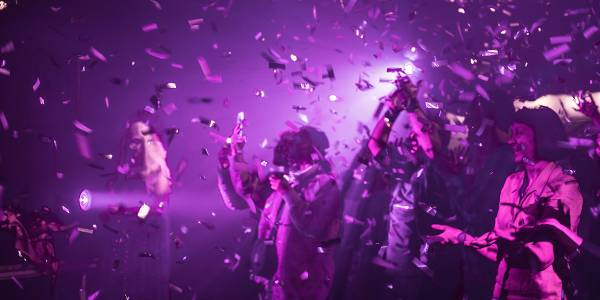 Hazy, purple lights wash over a group of people, who stand, arms outstretched, amid a burst of purple confetti.