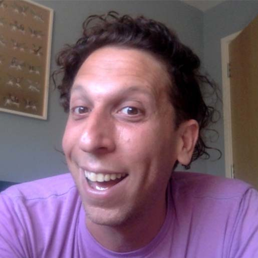 A white man with curly brown hair and a pink t-shirt smiles into the camera.