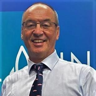 A middle aged white man in a shirt, tie and glasses is smiling. Behind him is a blue background.