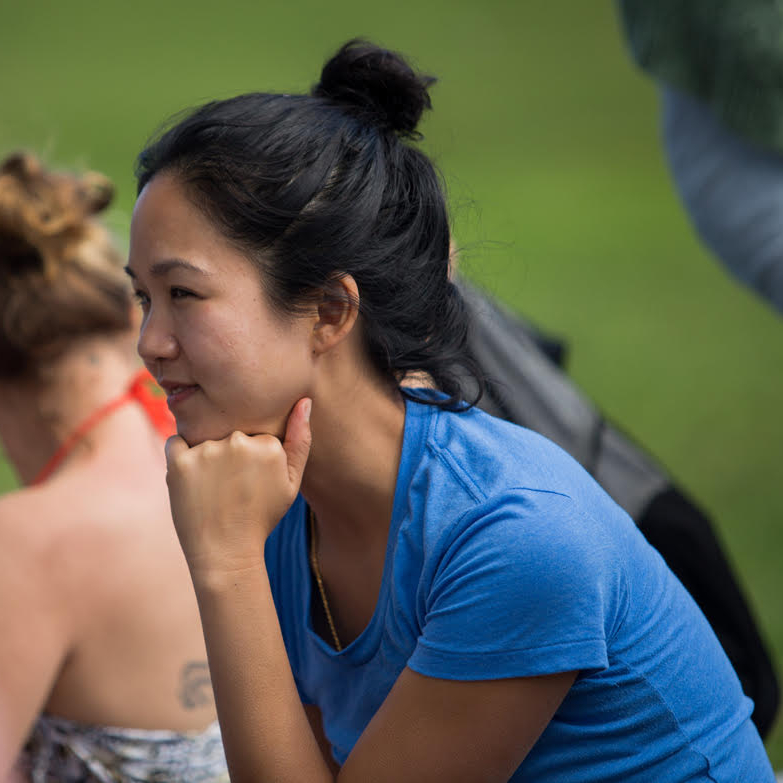 An Asian woman in profile wearing a blue t-shirt and her hair in a top knot. Her chin rests on her left fist.