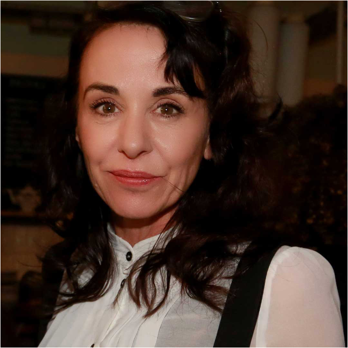 A white woman with long dark hair wearing a white shirt