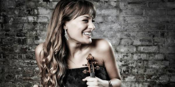 A young, white woman (Nicola Benedetti) with brown hair is at the centre of a picture, with a smokey grey brick wall behind her. Smiling, she turns her head to the right. The top of a violin can be seen by her right shoulder.