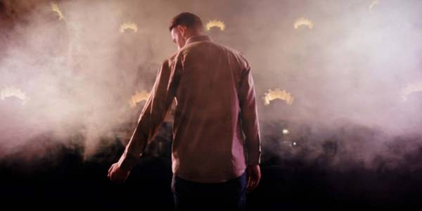 An image of the back Wayne Jackson on stage under dimmed lighting and smoke.