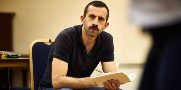 An image of Brian Mullin. They have brown short hair and a full moustache. They sit on a chair holding a script.