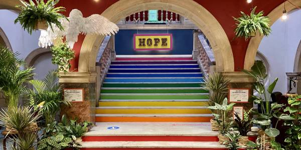 An image of the Battersea Arts Centre foyer. An alcove entrance over a grand rainbow stair case. To either side, there are plants hanging from the ceiling and gathered in pots on the floor. A yellow and pink sign saying 'HOPE' can be seen at the top of the steps.