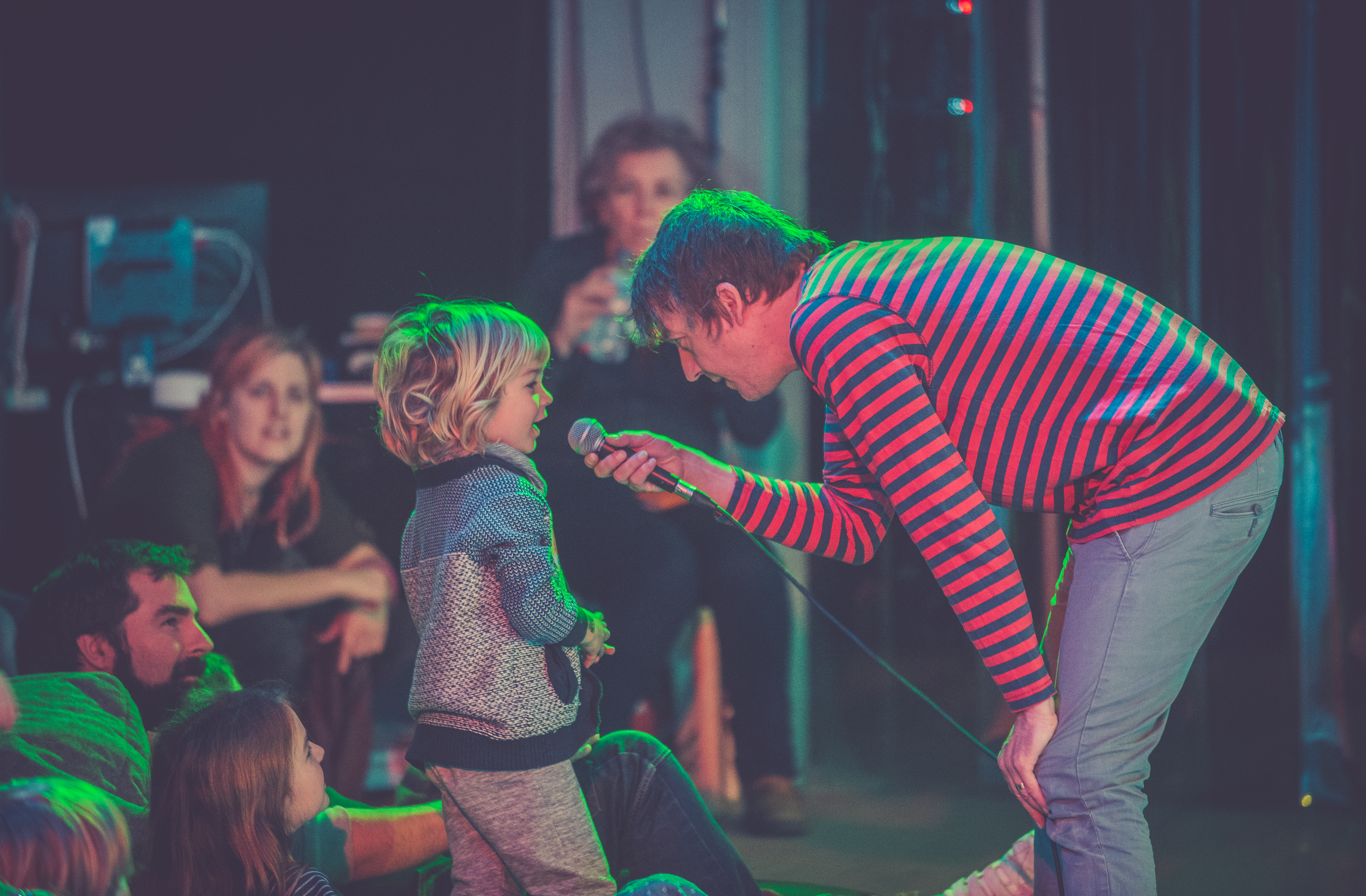 An image of an artist wearing a red and black striped long tshirt holds a microphone to a young child with blonde hair under green and pink flourescent lights.